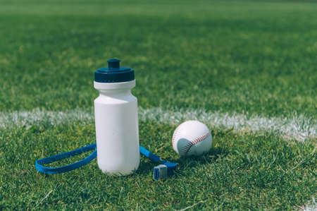 Sports water bottle with a whistle and a baseball ball in a green stadium
