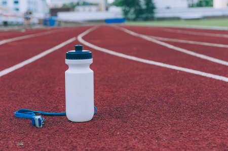 Sports bottle with water and a whistle in a stadium for running