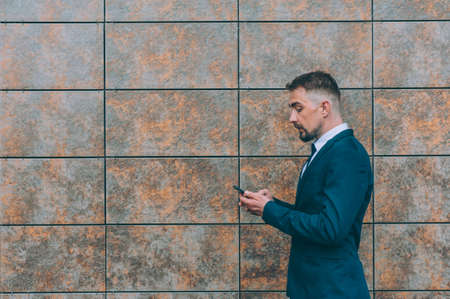Businessman in a blue jacket with a smartphone in his hand on a wall background