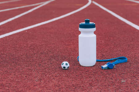 Sports water bottle with whistle and ball in a running stadium