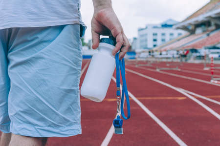 The athlete holds in his hands a sports bottle for water and a whistle in the stadium