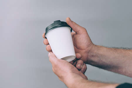 Mock-up for logos and design. A man holds in his hand a glass of coffee Stok Fotoğraf