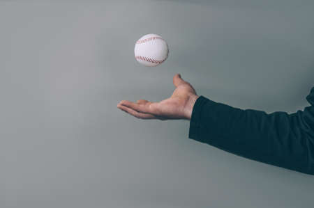 The guy holds a baseball ball in his hand on a gray background Imagens