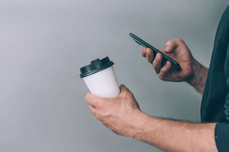 Mock-up for logos and design. A man holds in his hand a glass of coffee with a smartphone