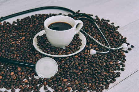 A medical tool on a background of coffee beans and a white cup