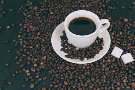 Cup for a drink with sugar on the background of coffee beans Stok Fotoğraf