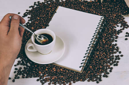 A man stirs coffee on a background of a notebook and beans