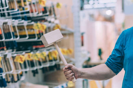 The buyer in the hardware store selects the goods. A man holds a wooden construction hammer in his hand Фото со стока