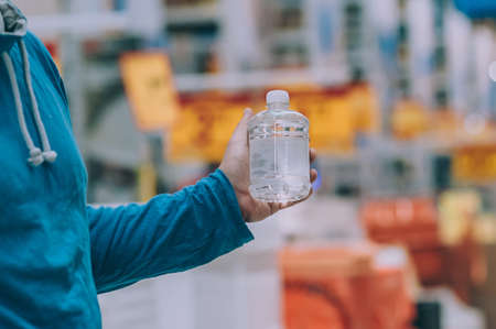 A buyer in a hardware store selects a product. A man holds in his hand a bottle of liquid Фото со стока