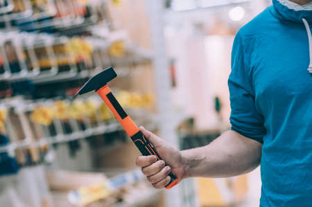 The buyer in the hardware store selects the goods. A man holds a metal construction hammer in his hand Фото со стока