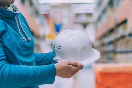 A buyer in a hardware store selects a product. A man holds in his hand a white construction helmet for the head