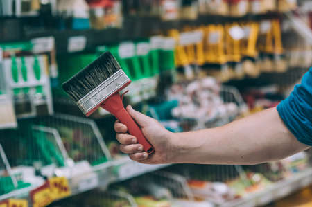 A buyer in a hardware store selects a product. A man holds a paint brush in his hand Фото со стока