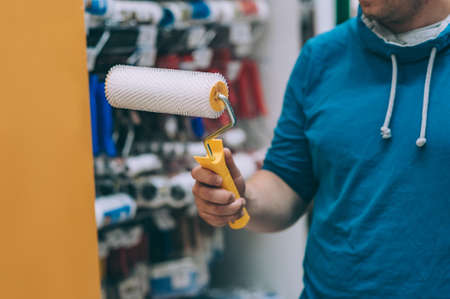 A buyer in a hardware store selects a product. A man holds a paint roller in his hand Фото со стока