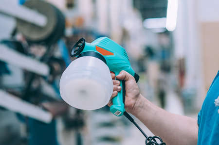 A man holds an electric spray gun in his hand. A buyer in a hardware store selects a product