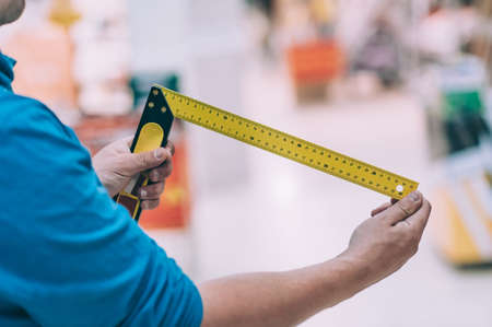 The buyer in the hardware store selects the goods. A man holds a metal measuring square in his hand Фото со стока