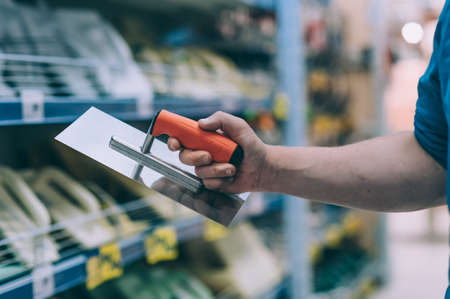 The buyer in the hardware store selects the goods. A man holds a metal spatula in his hand Фото со стока
