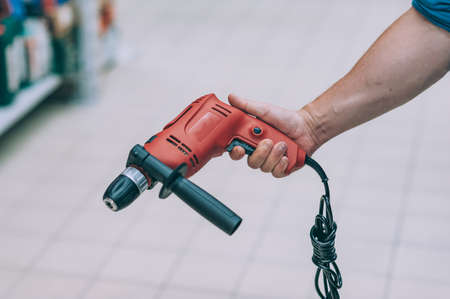 A man holds an electric drill in his hand for drilling. A buyer in a hardware store selects a product