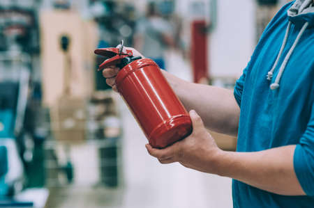 A man holds a fire extinguisher in his hand. A buyer in a hardware store selects a product Фото со стока