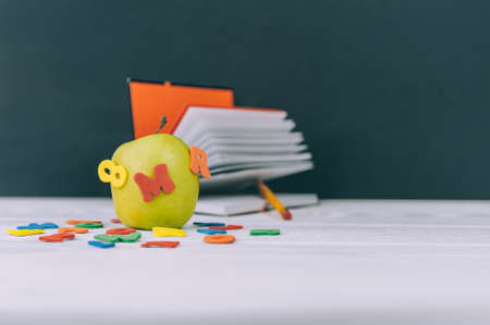 Concept Back to School. Green apple with colored letters and notepad background Standard-Bild
