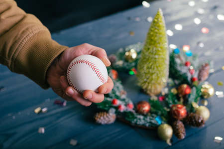 A man holds a baseball ball against the background with decoration on a wooden table. Festive composition for new year and christmas