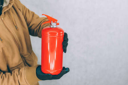 A man holds a red fire extinguisher in his hands on a white background Stock Photo