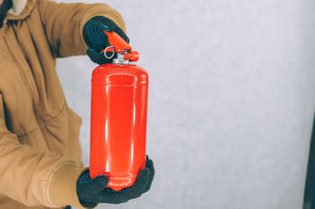 A man holds a red fire extinguisher in his hands on a white background
