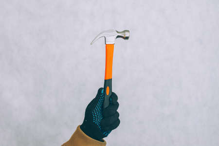 A man holds a construction hammer in his hands on a light background