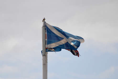 Scottish saltire and Union Jack flags flying in the wind on flagpoles