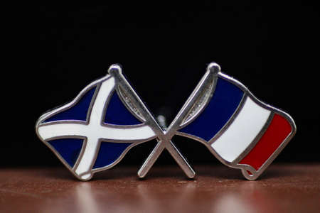 Macro close up of a lapel pin badge with crossed Scottish saltire and French Flag