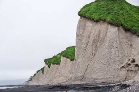 White hills with green top along the black sand coast Stock Photo