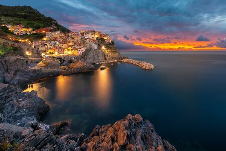 Sunset shot of the village Manarola at the sunset with calm sea and lights in the windos Archivio Fotografico - 129464048