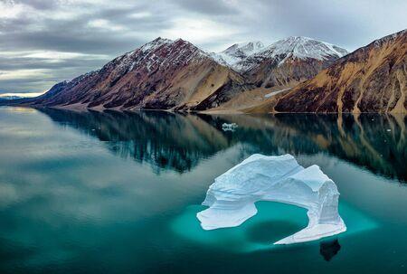 Paisaje del norte con un gran iceberg de forma redonda inusual con un gran agujero bajo el agua