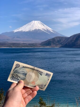 A hand holding a yen banknote with mount Fuji with the mound Fuji in the background 免版税图像