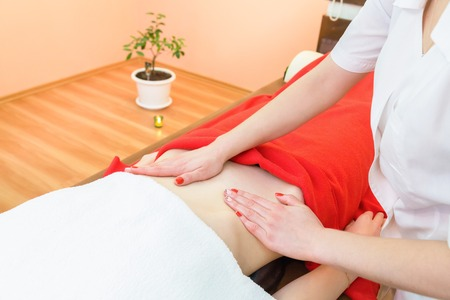 conducts: Masseur conducts anti-cellulite massage of the abdomen. Stock Photo