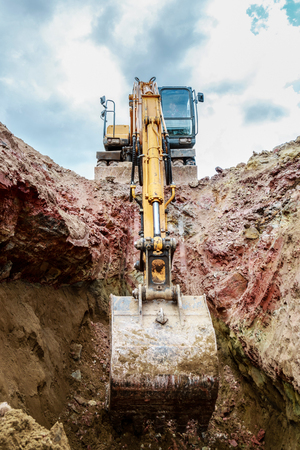 Excavator digging a trench. Lowered the bucket down. Stock Photo
