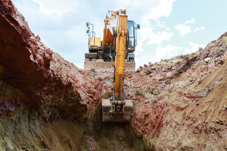Excavator digging a pit. Bucket crashed into the ground. Stock Photo