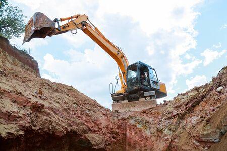 Excavatrice creuse une tranchée. Travailler sur le chantier de construction. Banque d'images - 81543657