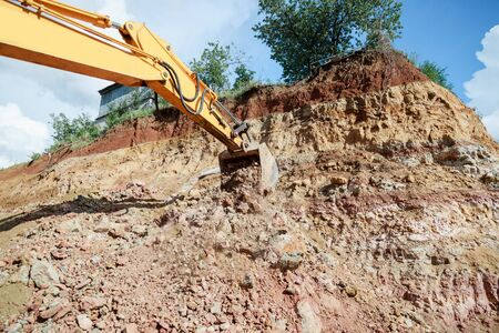 Excavator bucket with earth. Construction work on site.