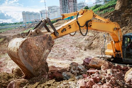 Excavator pours soil. View bucket closeup. Work on the construction site. Stock Photo