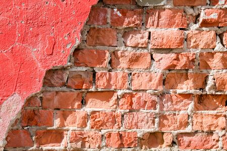 Old brick wall with chipped plaster. Background. Stock Photo