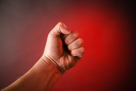 Male clenched fist on a red background Stock Photo