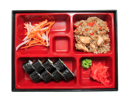 Bento lunch in the box. Set - sushi rolls, salad, pilaf, meat, sauce and wasabi. Isolated on white background.