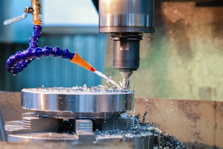 Drilling machine makes a hole in the metal product. Coolant is pouring on the drill.