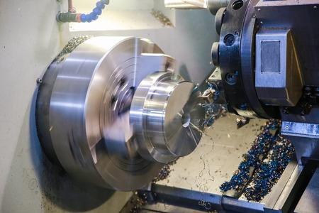 CNC lathe processes metal detail. Automated production.