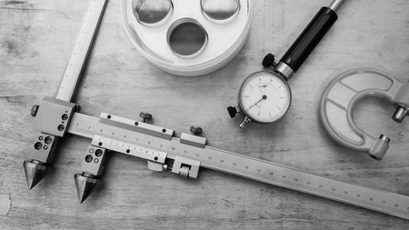 Metal measuring instruments on a wooden table. Product quality control.