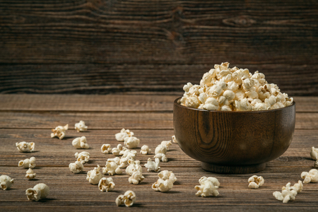 Popcorn in bowl on old wooden background. Copy space. Stockfoto