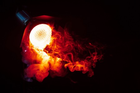 Red light with smoke on dark background. Equipment for photo Studio. Stockfoto