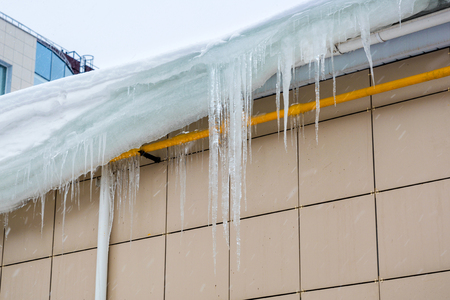 Large icicles hang from the roof. Danger to passersby. Banque d'images - 120779129