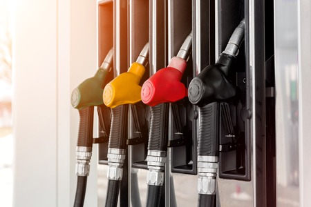 Green, yellow, red and black fuel pistols on fuel station. Closeup. Banque d'images - 120779154