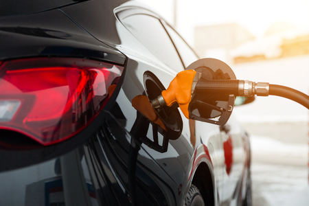 Black new car refuels at the gas station. Gun in the gas-tank. Stockfoto